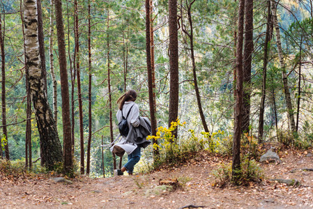 The girl walks along in the woods