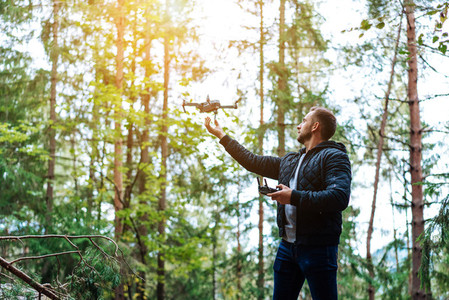 guy starts a quadrocopter in the forest