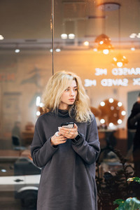 Blonde girl standing with smartphone