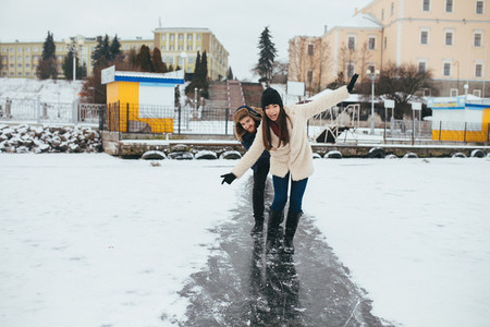 man and woman skate on ice