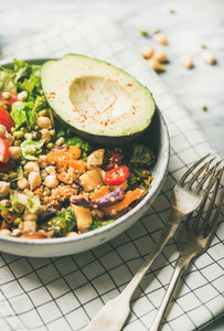 Vegan dinner with avocado grains beans and vegetables