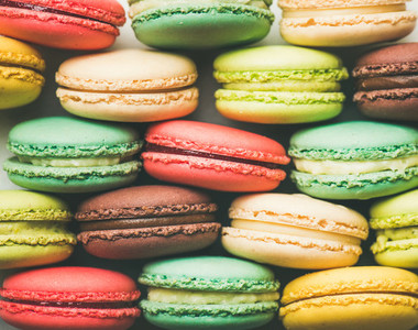 Colorful French macaroons cookies stacked in rows
