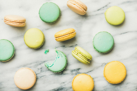 Colorful French macaroons over grey marble background  top view
