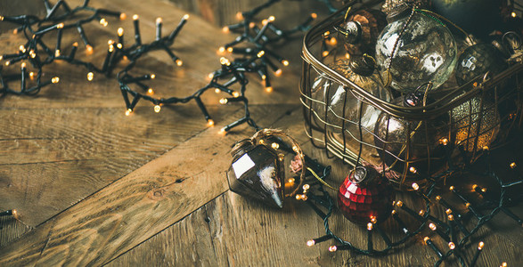 Christmas decoration balls in box and light garland  rustic background
