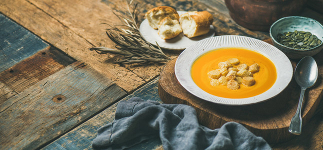 Warming pumpkin cream soup with croutons and seeds wide composition