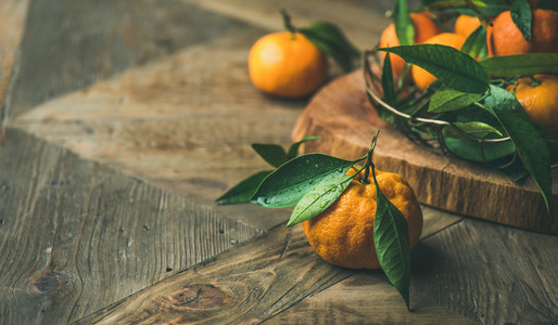 Fresh tangerines with leaves on board copy space horizontal composition