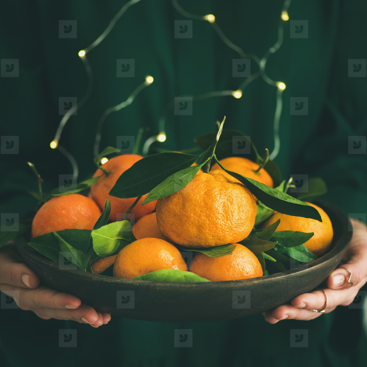 Fresh tangerine fruit in plate in female hands  square crop