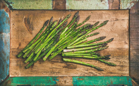 Raw uncooked green asparagus over rustic background horizontal composition