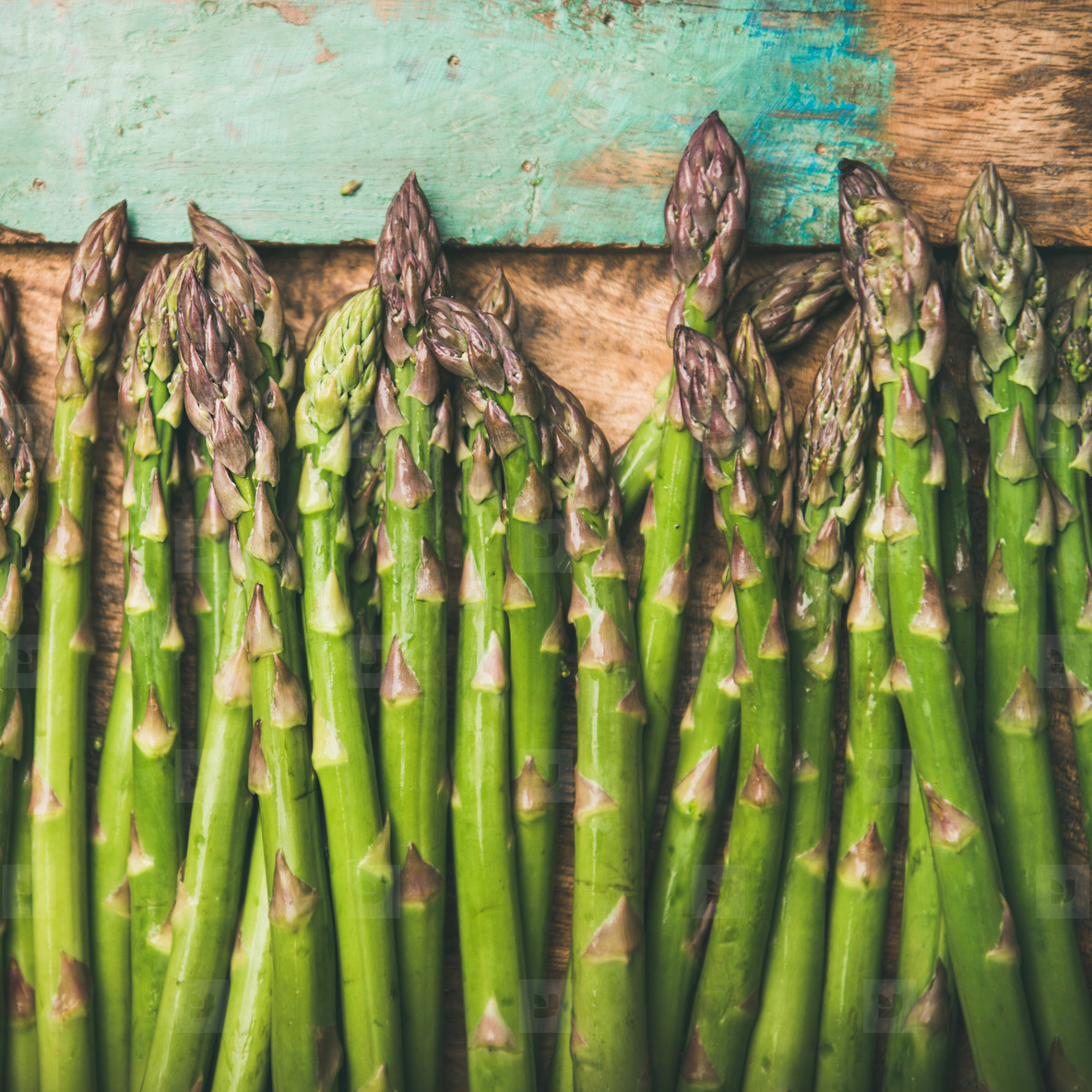 Raw uncooked green asparagus over rustic wooden tray background  square crop