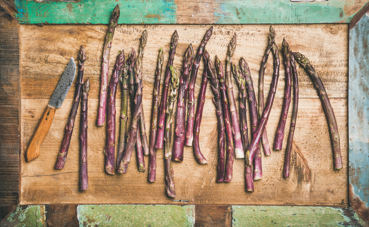 Fresh purple asparagus and knife over wooden tray background