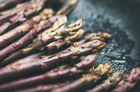 Fresh raw uncooked purple asparagus over dark background  horizontal composition