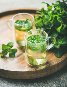 Hot herbal mint tea in glass mugs with leaves close up