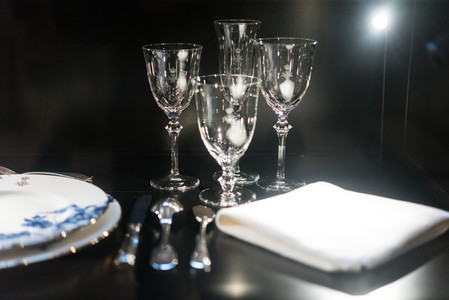 Glasses forks knives napkins on dark black table