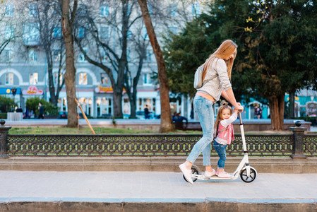 Mom and little daughter on a scooter