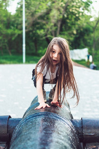 preschool girl crawls on top of cannon