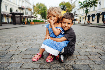 little boy and girl are sitting on the street