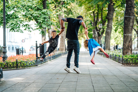 Children having fun with dad in the park