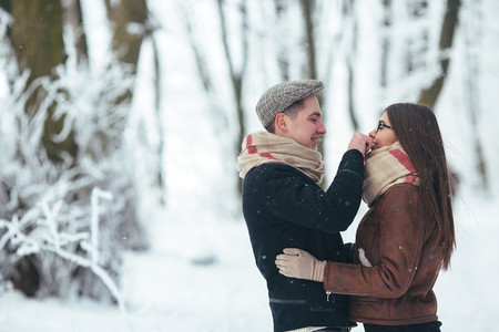 Happy couple playful together during winter holidays vacation outside in snow park