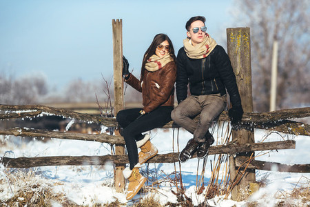 young couple sitting on old fence