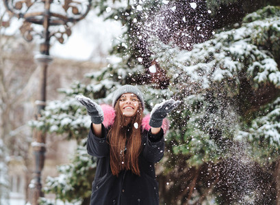 The girl throws snow up in the city