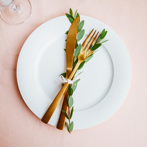 Festive table setting for celebrate event with decorated golden cutlery on a white table Top view flat lay