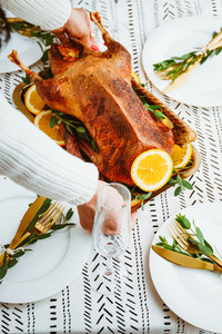 Woman sets a golden tray with whole roasted goose on a festive table   Thanksgiving or Christmas family dinner