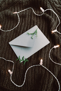 Top view on blank envelope on a warm sweater surrounded festoon lights Cozy fall or winter flat lay