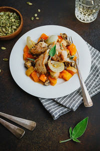 Seasonal autumn low calorie recipe from baked turkey medallions with pumpkin  onion  champignons and sage on a white plate