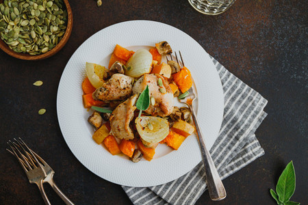 Top view on seasonal autumn low calorie recipe from baked turkey medallions with pumpkin onion champignons and sage on a white plate