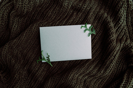 Blank sheet on a warm sweater  Cozy fall or winter mockup for text  Flat lay  top view