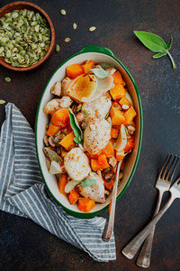 Top view on seasonal autumn low calorie recipe from baked turkey medallions with pumpkin onion champignons and sage in a ceramic dish
