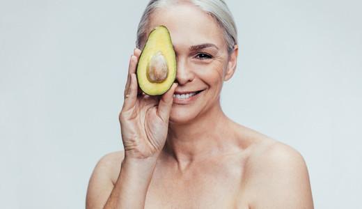 Senior woman with a half avocado
