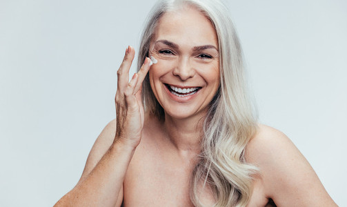 Woman applying anti aging cosmetic