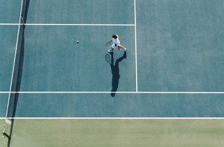Professional tennis player playing on club court