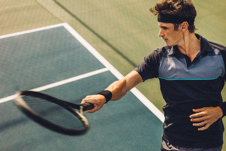 Tennis player hitting forehand from baseline