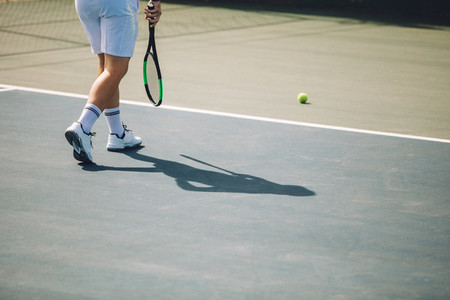 Tennis player walking on the hard court
