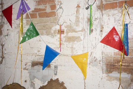 Multicolor bunting hanging on brick wall 01