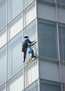 Harnessed window washer cleaning highrise windows 01