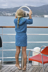 Curious girl on cruise ship looking through viewfinder at ocean 01