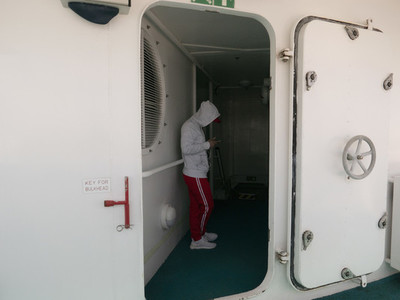 Young man using smart phone in doorway on cruise ship 01