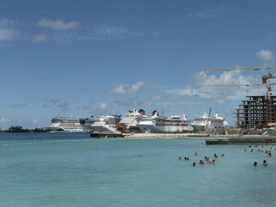 Tourists swimming in sunny ocean with cruise ships in background 01