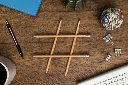 View from above pencils forming hash tag on wooden desk 01