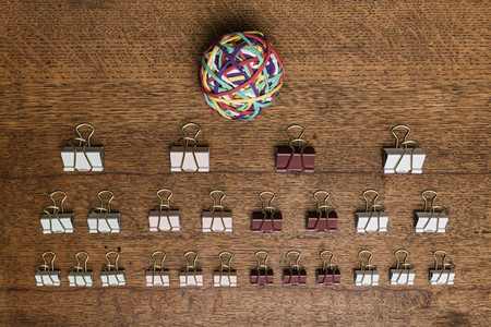 View from above binder clips and rubber band ball on wooden desk   knolling 01