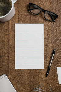View from above blank lined notepad on wooden desk 01