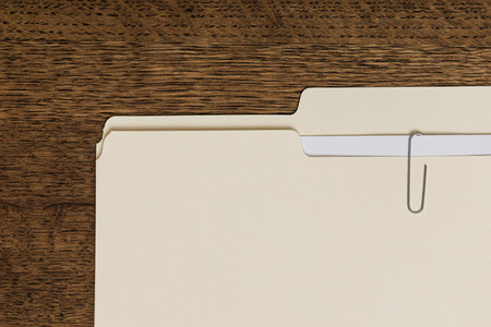 View from above manila folder and paperclip on wooden surface 01