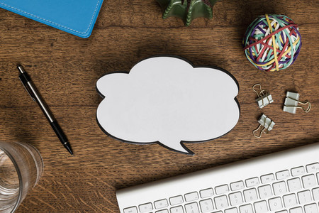 View from above paper speech bubble above computer keyboard on wooden desk 01