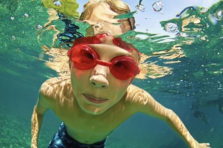 Portrait boy in swimming goggles swimming underwater 01