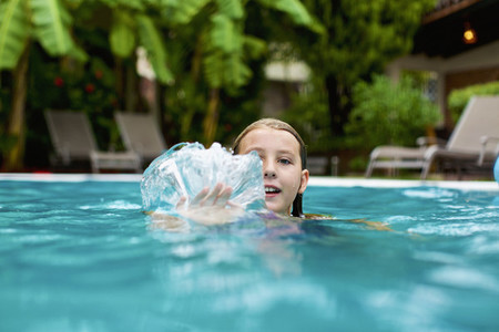 Portrait smiling girl swimming splashing hand in swimming pool 01