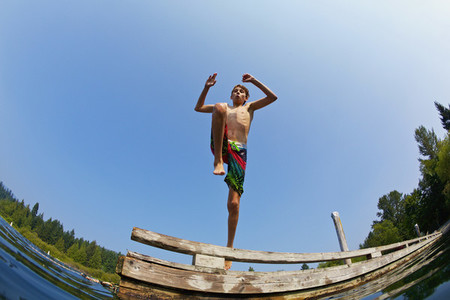 Boy jumping off dock into sunny lake 01