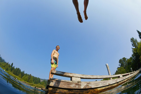 Boys jumping of dock into sunny summer lake 01